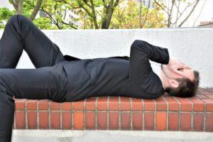 ベンチで横になるビジネスマン