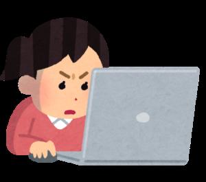 ノートPCをにらむ女性